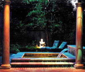 A landscape lighting design by Possidento Lightscapes adds nighttime ambience to a peaceful fountain